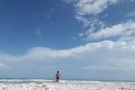 Girl standing in the ocean off the coast of the Sanibel Island near Fort Myers, Florida